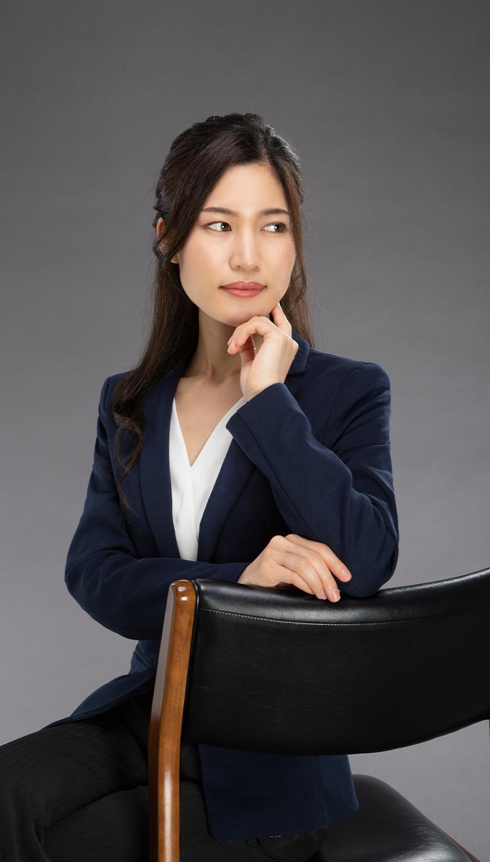 http://椅子に肘をついて振り返る女性