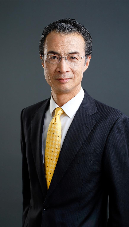 http://黒スーツに黄色のネクタイを締めた眼鏡の年配男性